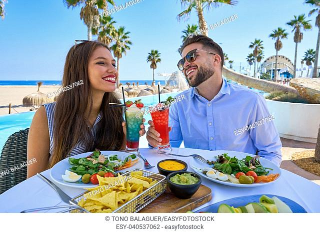 Young couple with cocktails in a swimming pool restaurant