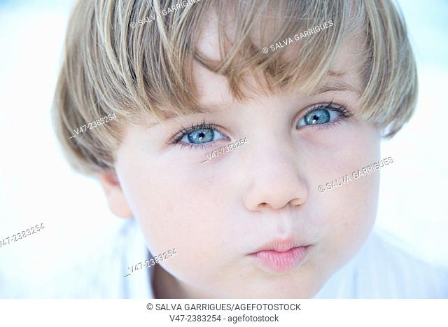 Portrait of a boy with blue eyes giving an air kiss