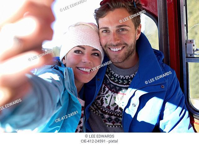Couple talking selfie in ski lift