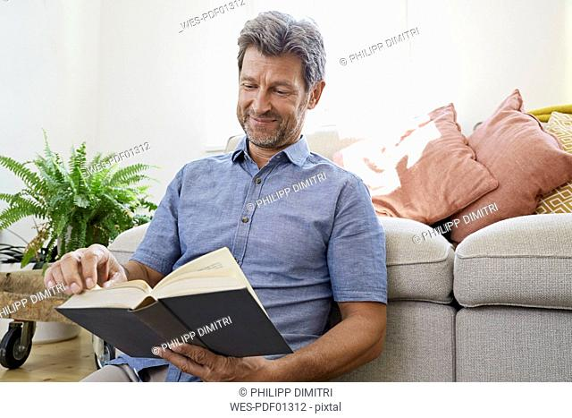 Mature man at home sitting in front of couch, reading book