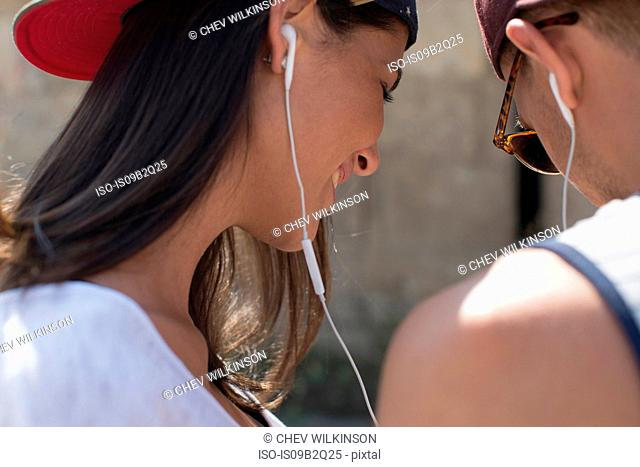 Couple wearing and sharing earphones