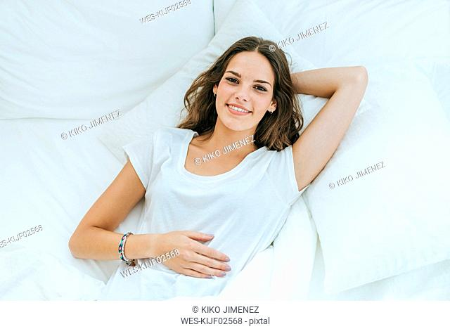 Top view of happy young woman lying in bed