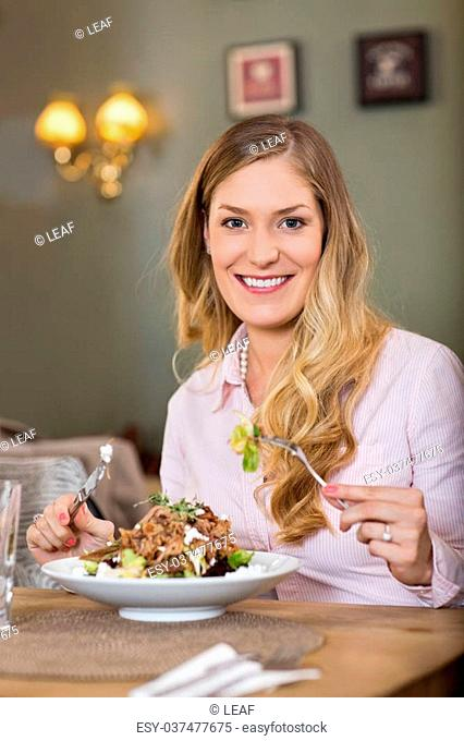 Portrait of happy young woman having meat salad at restaurant
