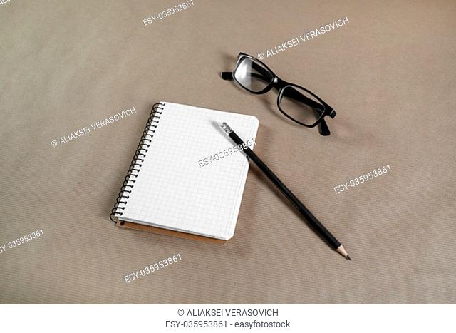 Blank paper notebook with glasses and pencil on craft paper background. Business concept. Stationery set. Responsive design template