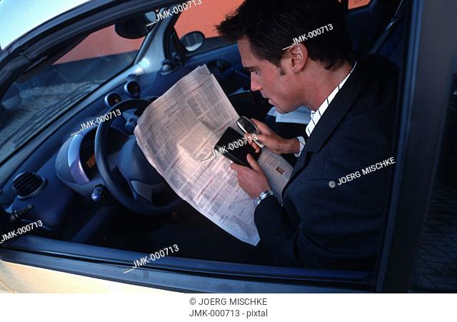 A salesman, businessman, tradesman, employee, officer, young man sitting in a car reading a newspaper