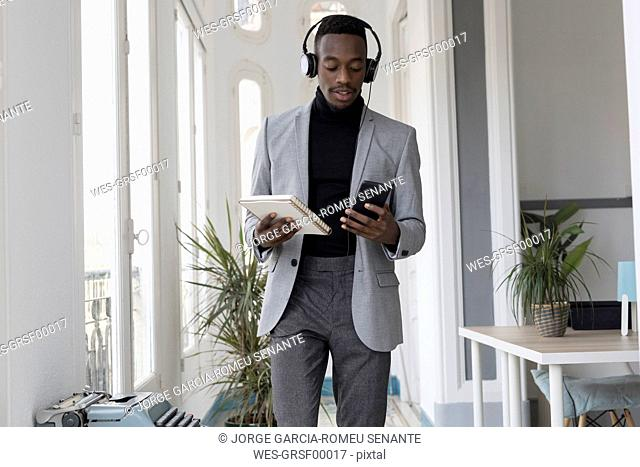 Portrait of young businessman with headphonbes and notebook in the office looking at cell phone