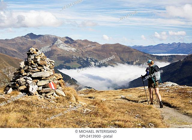 Female hiker along a trail on top of a mountain with large stone marker and cloud in the valley; Hintertux, Austria