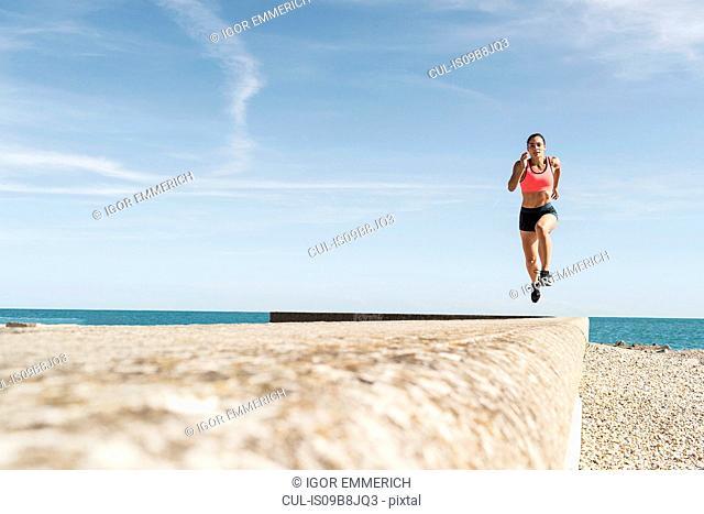 Young woman running along sea wall, mid air