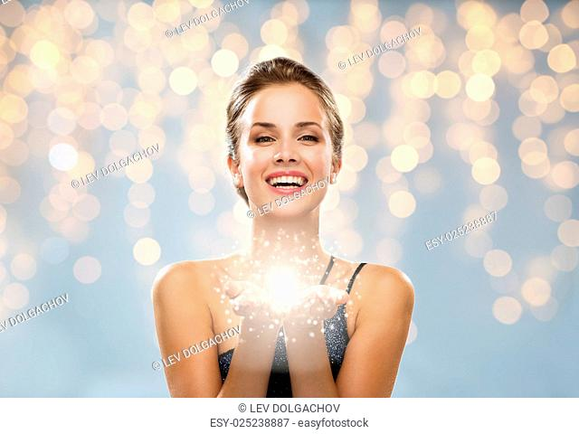 people, holidays, magic and luxury concept - happy woman dress with fairy dust on parms