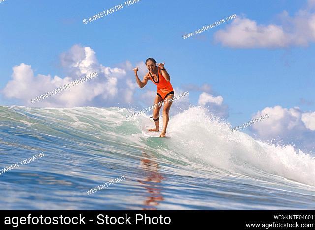 Female surfer with shaka sign