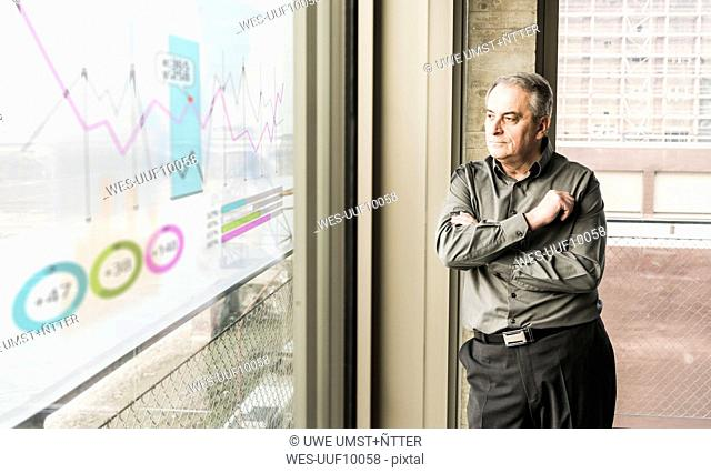 Businessman looking at windowpane with data in office