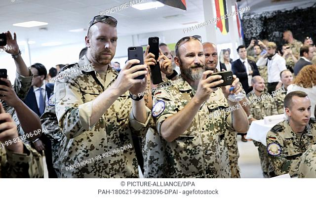 21 June 2018, Jordan, Amman: German Armed Forces soldiers photographing the German chancellor at the German air base near Amman