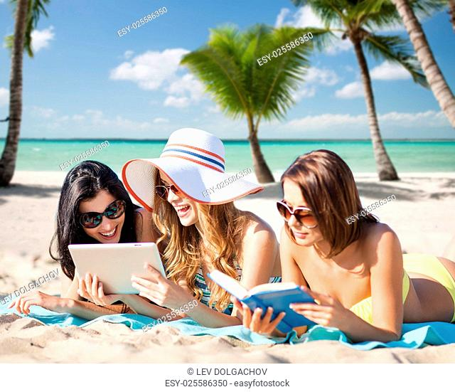 summer holidays, technology, people, travel and internet concept - happy young women in bikinis with tablet pc and book sunbathing over exotic tropical beach...