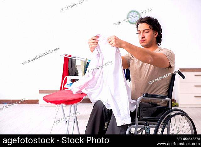 The young man in wheel-chair doing ironing at home