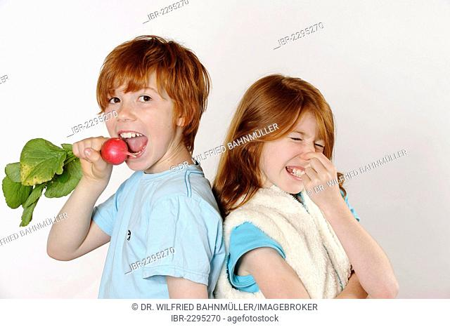 Boy eating radishes, girl rejecting raw food or vegetables
