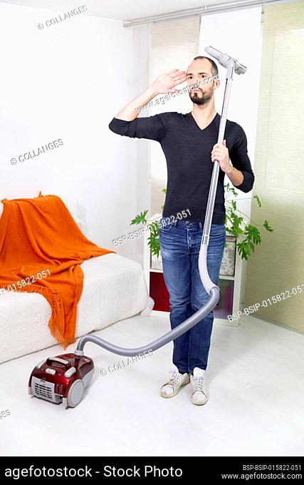 A man pretending to be a soldier with a vacuum cleaner
