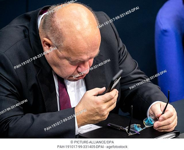 17 October 2019, Berlin: Peter Altmaier (CDU), Federal Minister of Economics and Energy, looks at his mobile phone in plenary