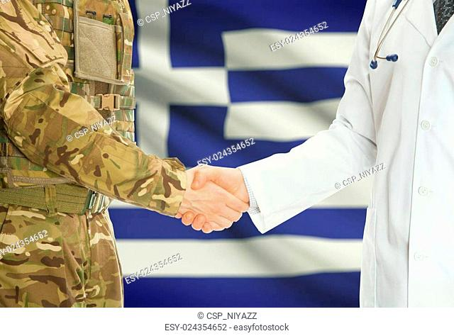 Military man in uniform and doctor shaking hands with national flag on background - Greece