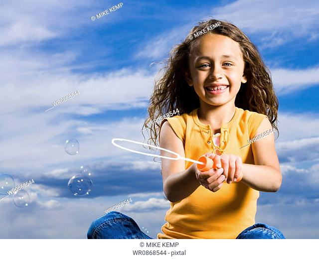 Girl outdoors with bubbles smiling