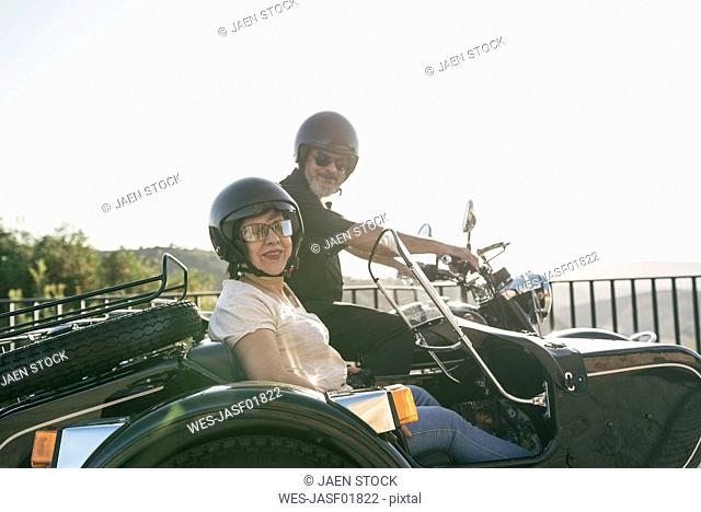 Spain, Jaen, mature couple on motorcycle with a sidecar on a bridge