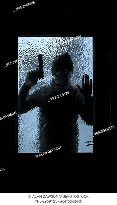 Silhouette of man holding gun looking through house window