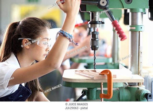 Serious student using drill in vocational school