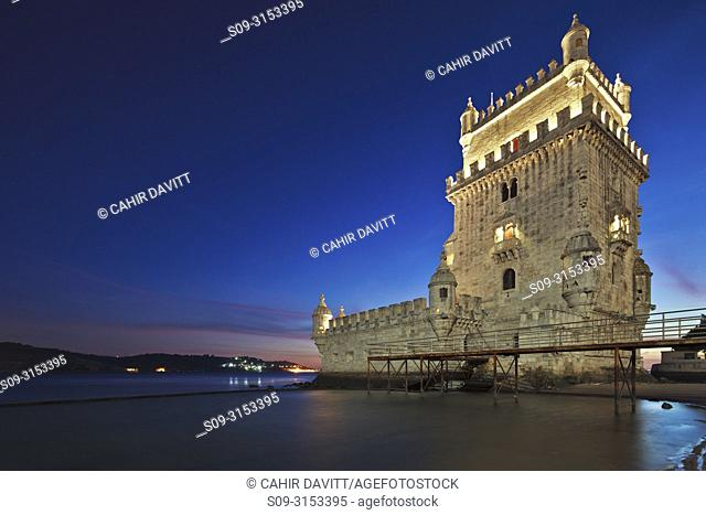The early 16th century Portuguese Manueline Style, Torre de Belem designed by the architect Francisco de Arruda at twilight with the River Tagus Estuary in the...
