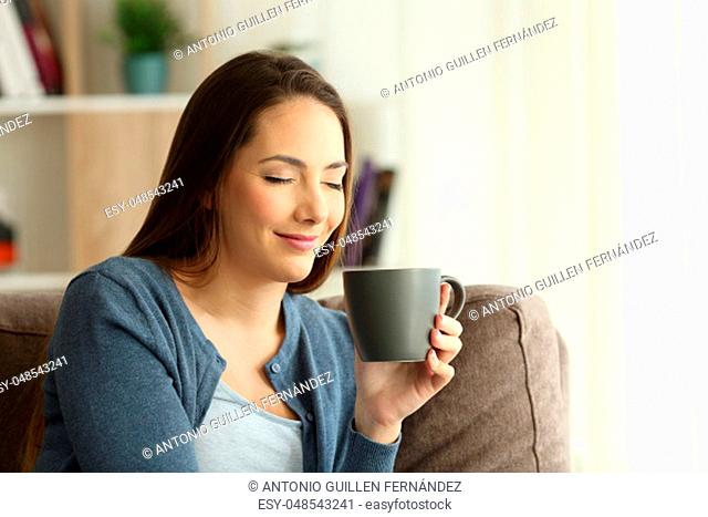 Relaxd woman enjoying a cup of coffee sitting on a couch in the living room at home. Chill out concept