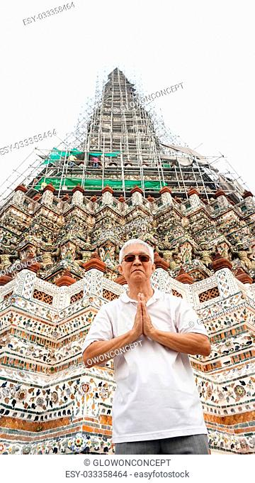 Asian senior man visiting temple of dawn, sawasdee act