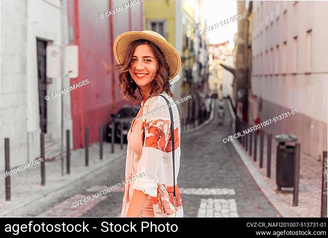 Young woman in a hat smiling and walking on a small street of Europe