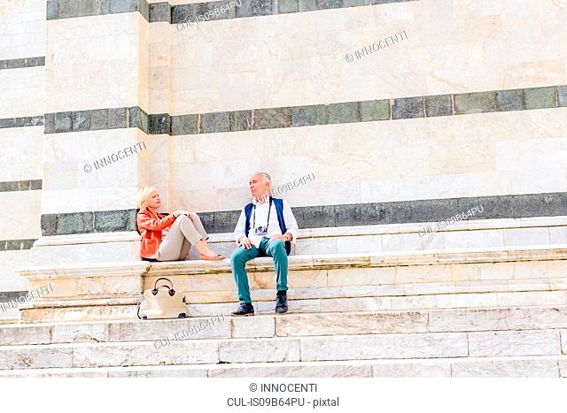 Tourist couple sitting on Siena cathedral stairway, Tuscany, Italy