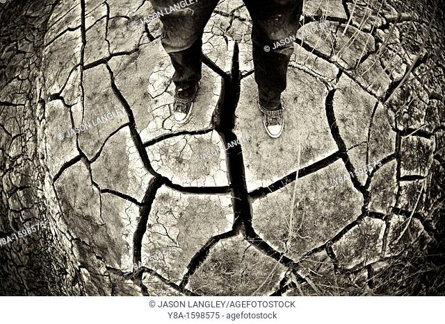 Person Standing on dry, cracked ground in a dried stream bed during a desert drought  Big Bend National Park, Texas, United States