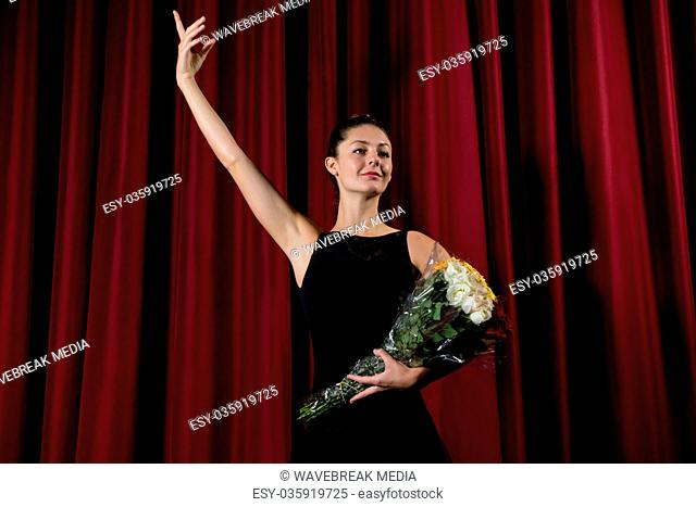 Ballerina posing with flower bouquet on stage