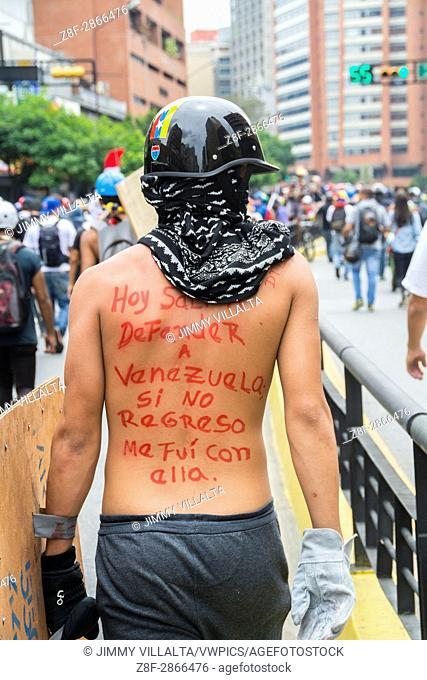 """A boy has written on his back: Today I went out to defend Venezuela, but I went back with her. Groups of young people, """"""""warriors"""""""" with their shields"""