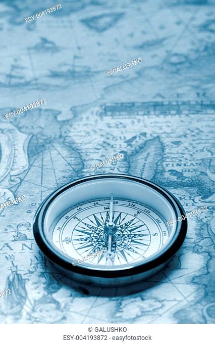 Old compass on ancient map
