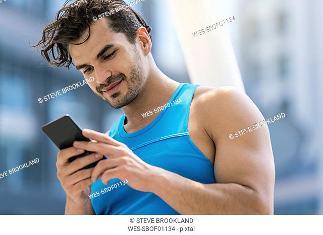 Runner checking messages on his smartphone