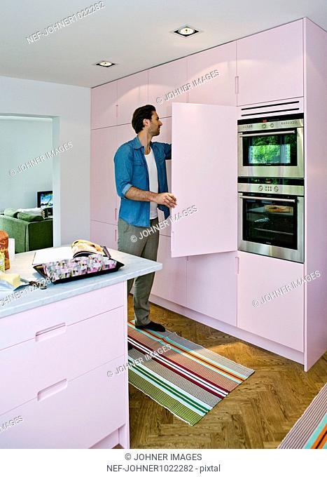 Scandinavia, Sweden, man opening door to kitchen cupboard