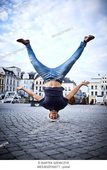 Man having fun doing headstand on square in the city