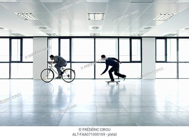 One businessman riding bicycle, the other skateboarding