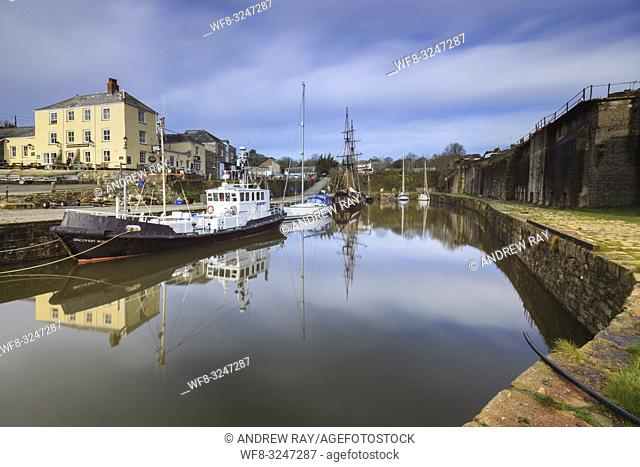 Boats reflected in the dock at the Edwardian Port of Charlestown on the south coast of Cornwall