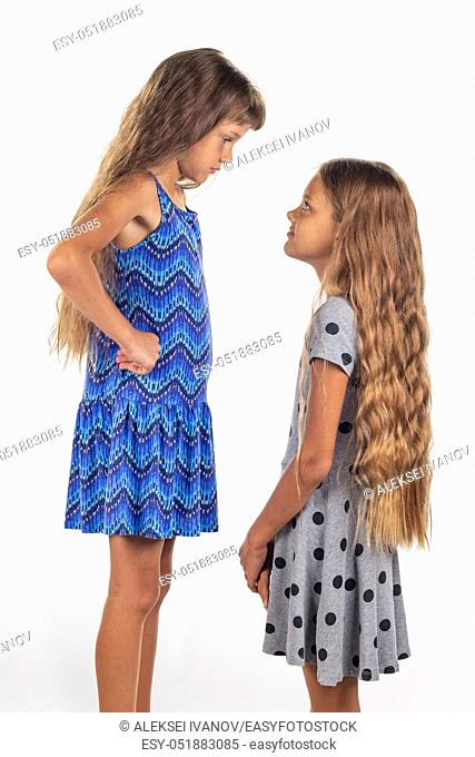Two girls of different stature, one of them stood on a chair to be taller than the other