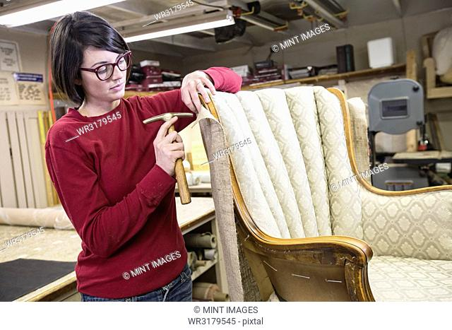 A young female upholsterer using a tack hammer on a chair in an upholstery shop