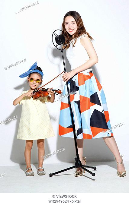 The little girl and her mother play the violin
