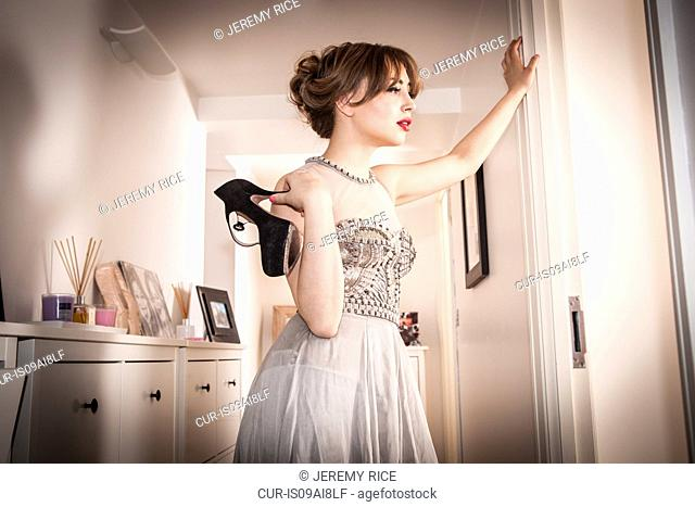 Tired young woman in evening gown in hallway