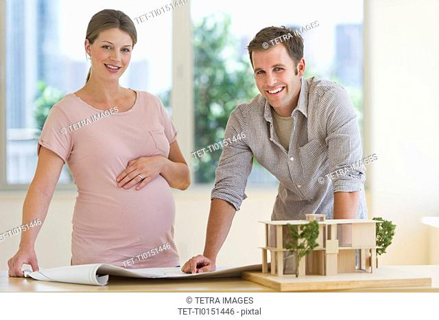 Young couple with blueprints and house model
