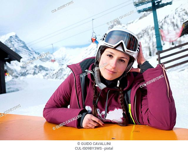 Young woman skier at table in snow covered landscape, portrait, Alpe Ciamporino, Piemonte, Italy