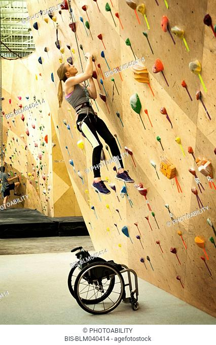Paraplegic woman rock climbing in gym