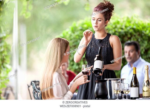 Waitress showing wine bottle to woman in restaurant
