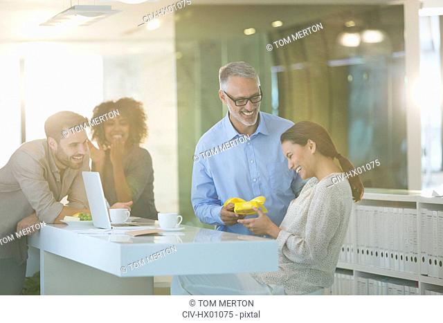Businessman giving gift to businesswoman in office