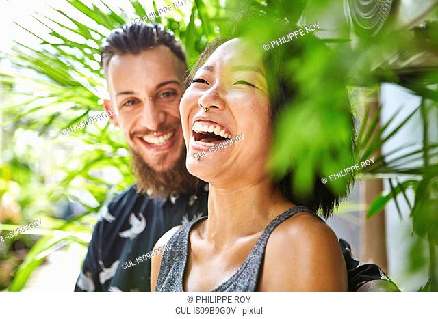 Multi ethnic couple laughing together in residential alleyway, Shanghai French Concession, Shanghai, China